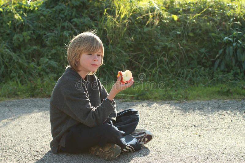 Sitting boy eating an apple stock photo