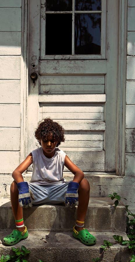 Sitting boy on steps. A young boy sitting sadly on steps stock photos