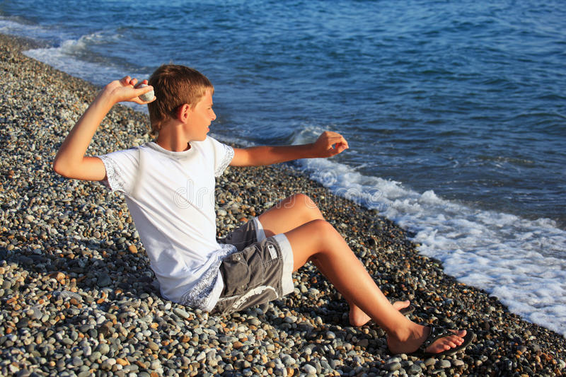 Sitting boy throws stone in sea royalty free stock image