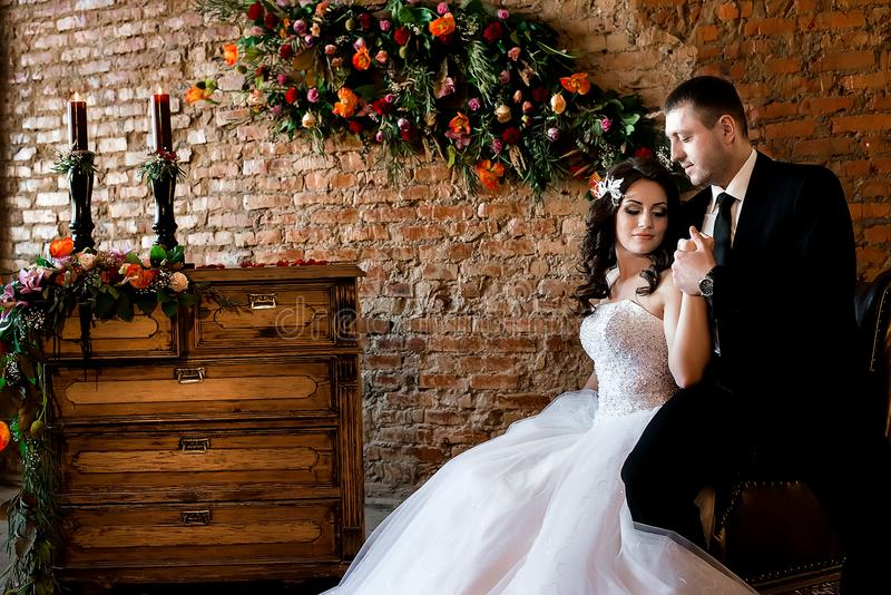 Sitting bride holding her man`s hand and smiling stock image