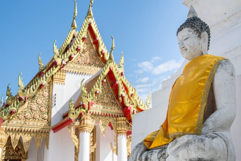White buddha with yellow clothes near temple stock photos