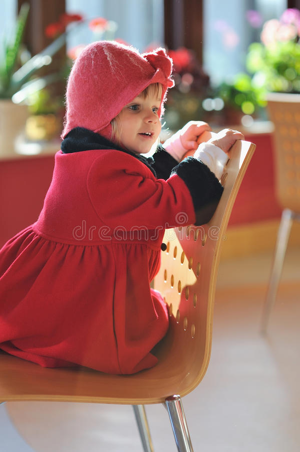 Sitting on a Chair. A little girl sitting on a wooden chair royalty free stock image