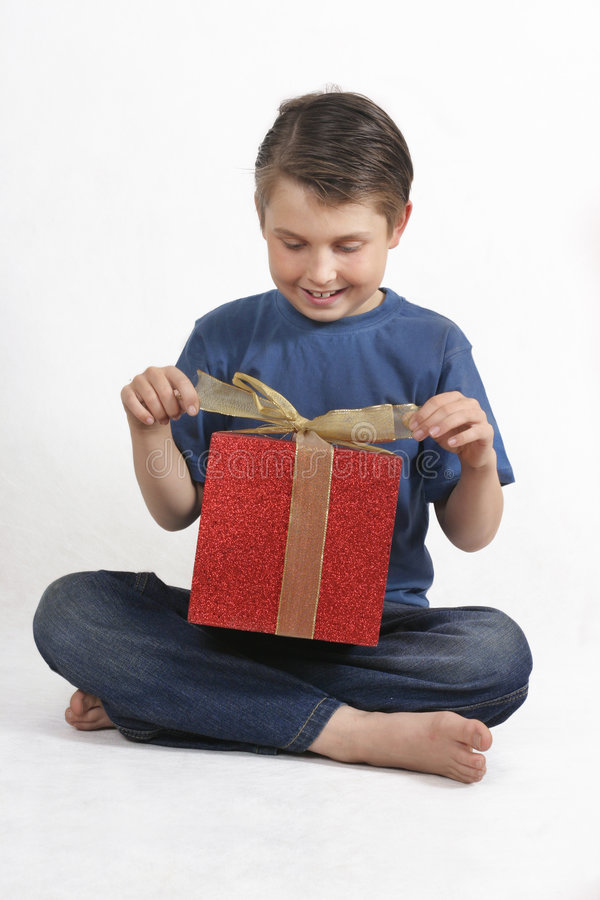 Sitting Child Opening A Present Royalty Free Stock Photo