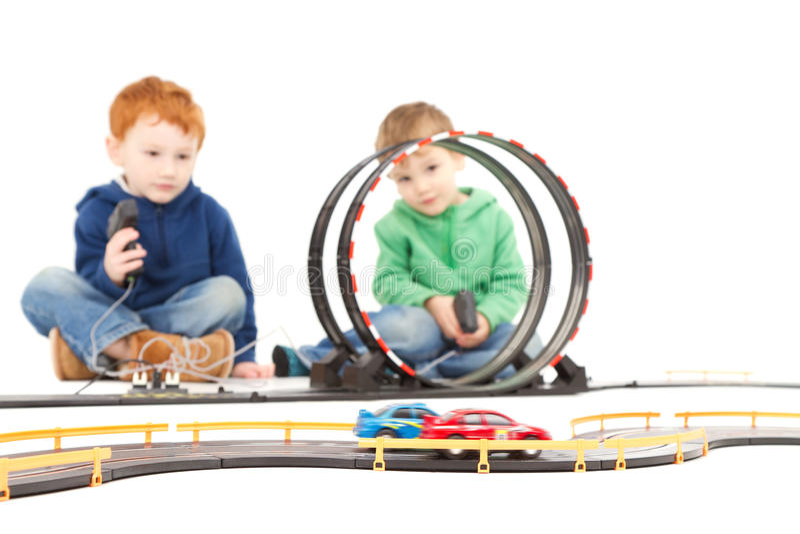 Sitting children playing kids racing toy car game. Sitting children playing kids racing toy electric slot car game. On white royalty free stock photos