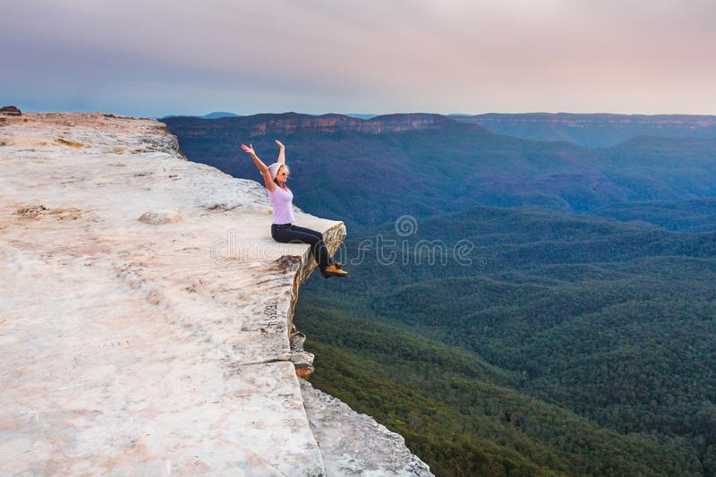 Sitting on the cliff edge feeling free. Woman showing emotional feelings of freedom and exhilaration sitting on the edge of the cliff overlooking the valley royalty free stock photo