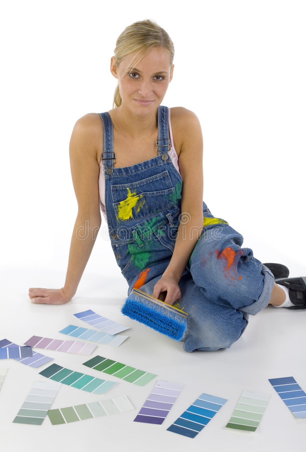 Sitting among colors. Young smiling blonde wearing dungarees with paintbrush in hand. Sitting on floor nearby color palettes. Looking at camera. Whole body royalty free stock photo