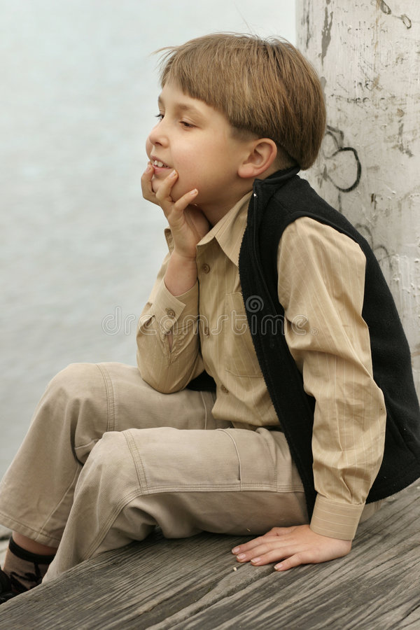 Sitting on the dock of the bay. Boy relaxing on the dock royalty free stock photos