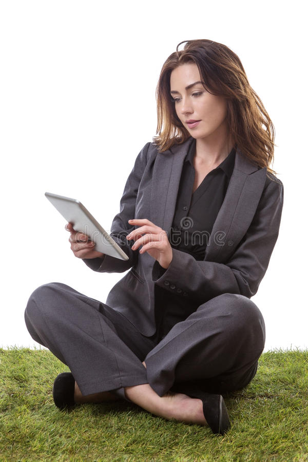 Sitting down working. Pretty brunette, sitting on the grass in a business suit holding her tablet computer, isolated on white stock photos