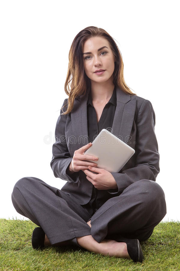 Sitting down working. Pretty brunette, sitting on the grass in a business suit holding her tablet computer, isolated on white royalty free stock photos