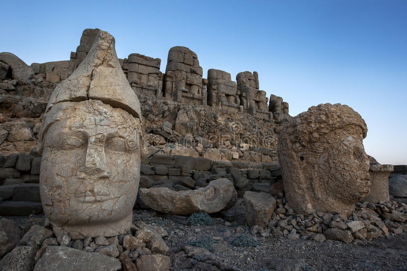 Sitting on the eastern platform of Mt Nemrut in Turkey are the statues of Apollo left and the goddess Tyche of Commageme. The Mt Nemrut National Park is stock photography