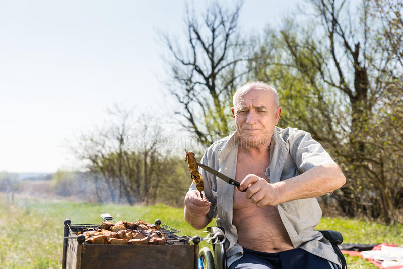 Sitting Elderly Man Holding Grilled Meat and Knife. Elderly Man with Unbuttoned Shirt and Sitting on his Wheelchair Holding Grilled Meat on Stick and Knife and stock image