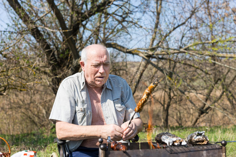 Sitting Elderly Man Roasting Meat at Campground. Sitting Elderly Man Roasting Meat on Stick for his Meal Seriously at the Campground Alone stock image