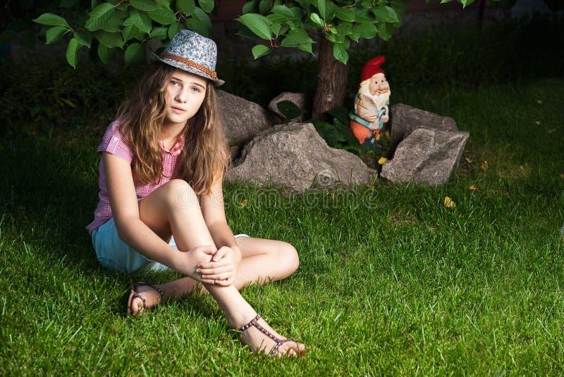 sitting för gräs- äng för G-flicka nästa till treen fotografering för bildbyråer