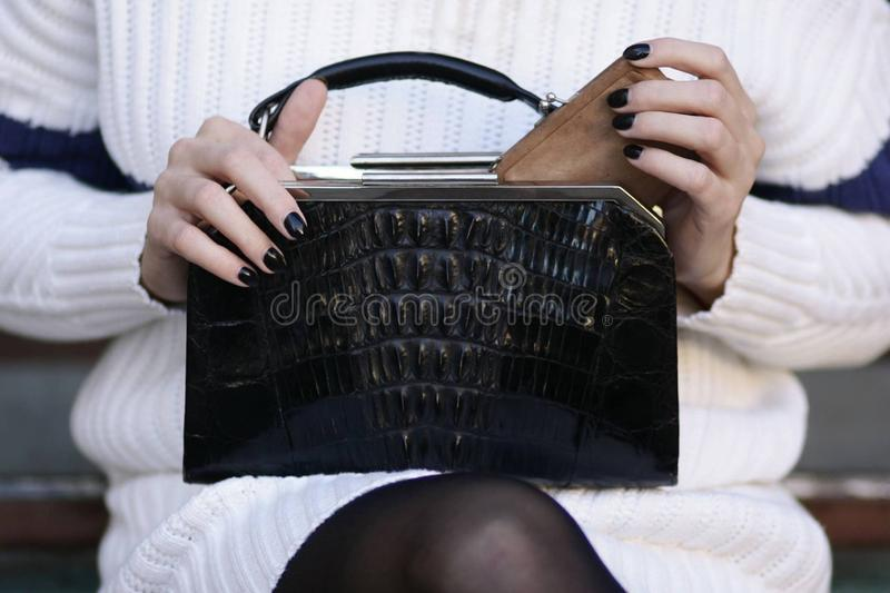 Black art deco crocodile purse and white sweater fashion detail stock image