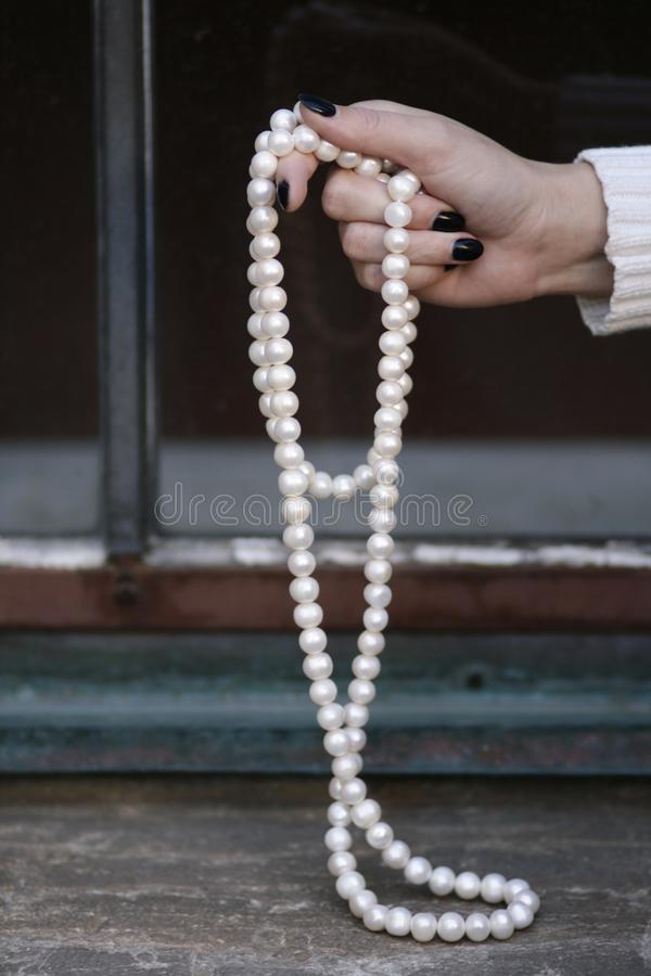 Female hand holding pearls outdoor fashion stillife. Sitting female body part with hand holding pearls necklace outdoor stillife detail with legs royalty free stock photos