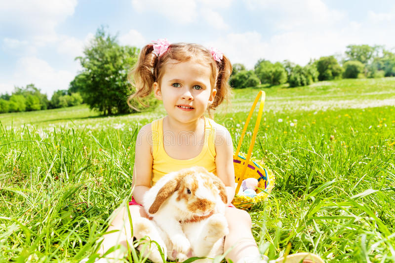 Sitting girl with cute rabbit in the park royalty free stock images