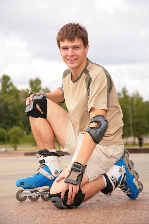 Sitting Guy on roller skates stock photos