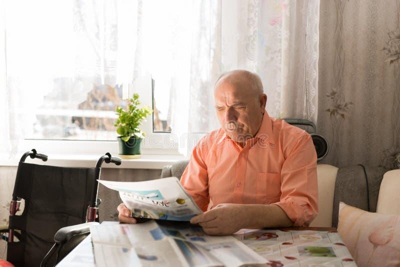 Sitting Happy Senior Man Reading Newspaper royalty free stock images