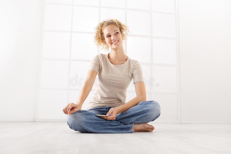 sitting happy woman smiling with cell phone, curly hair and dressed in jeans and T shirt isolated on white room background on flo stock photos