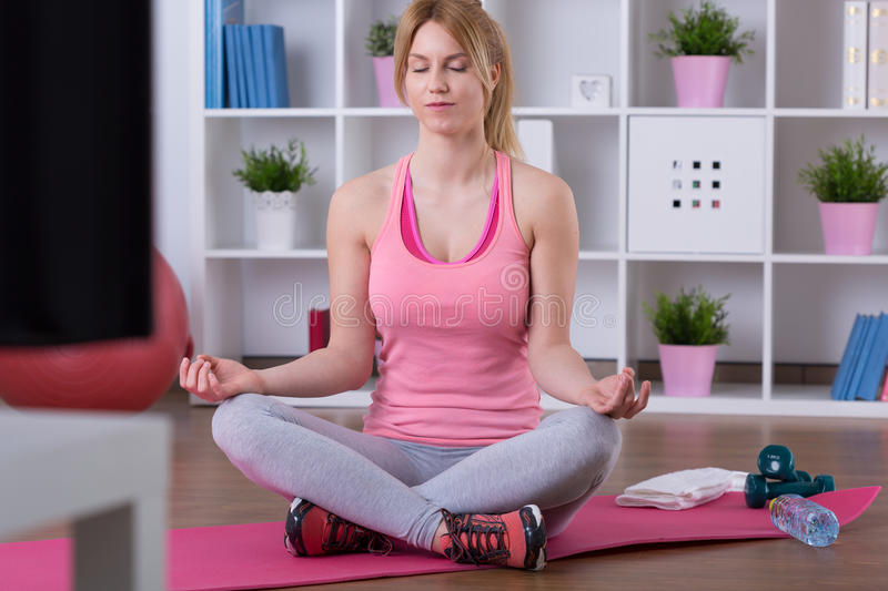 Sitting in lotus position. On exercise floor mat royalty free stock photo