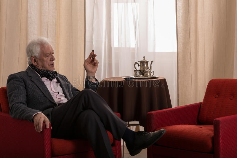 Sitting in lounge. Older rich man sitting alone in his stylish lounge royalty free stock photography