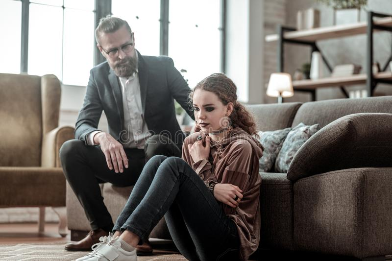 Teenager with black eye shades having depression sitting near father stock images