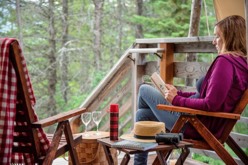 Sitting outside cabin reading a book stock photo