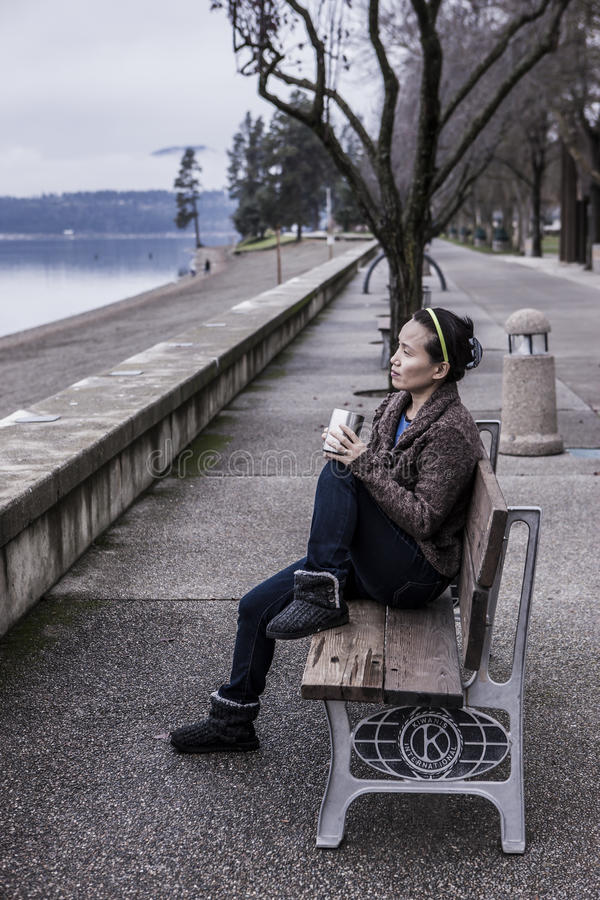 Sitting on park bench with her coffee. royalty free stock photo