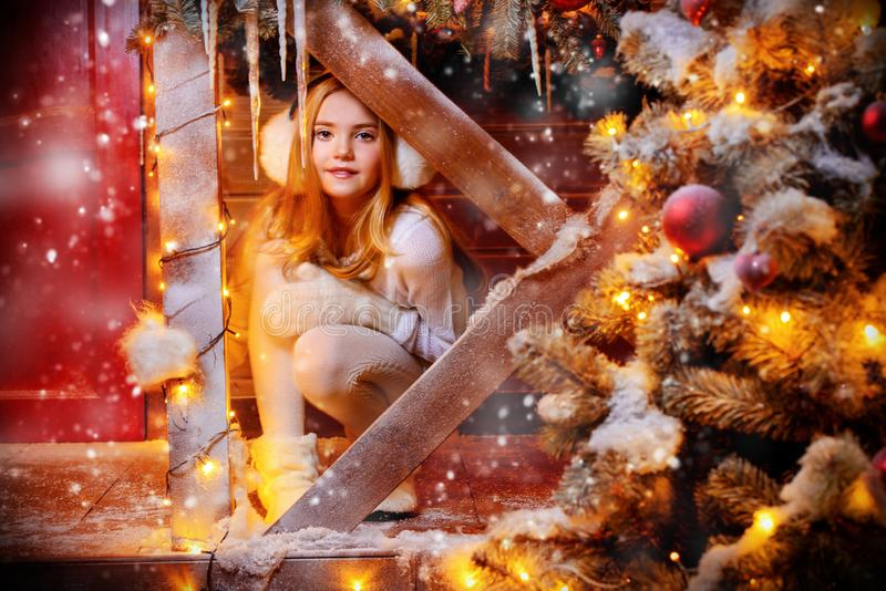 Sitting on the porch. Cute and pretty girl is in front of her house decorated for Christmas. Merry Christmas and Happy New Year royalty free stock image