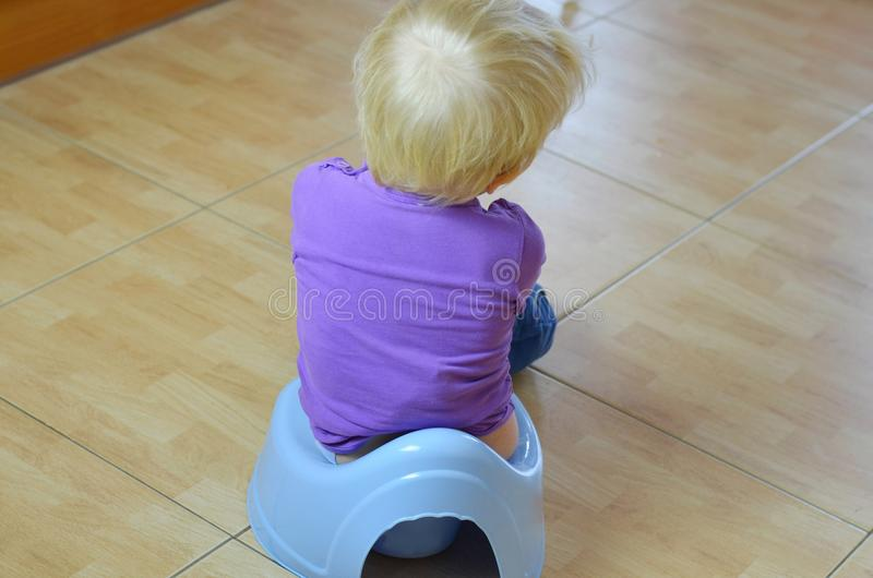 Sitting on a potty. Little child is training potty. Child is sitting and boring royalty free stock images