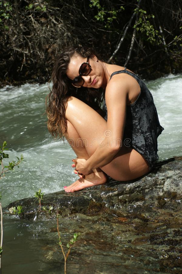 Sitting by the River. Women with sunglasses sitting on a rock by the torrent of a mountain stream stock photography