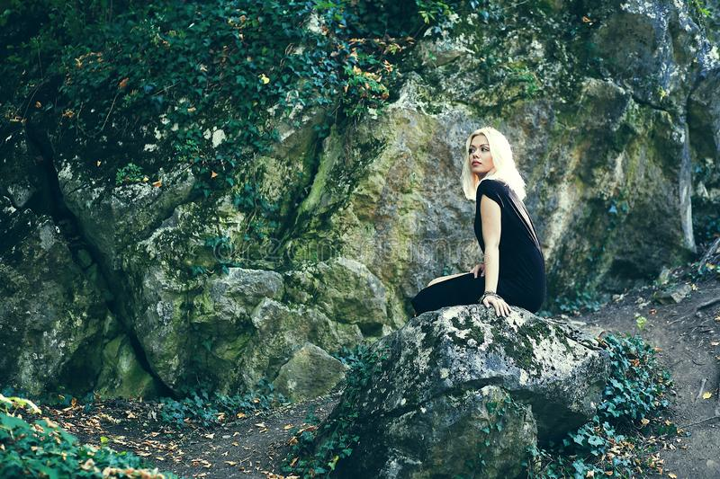 Sitting on the rock. Woman sitting on the rock on the mountain hill royalty free stock photos