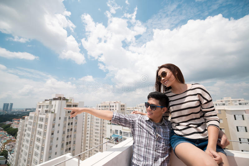 Sitting on the roof. Young men pointing at something while he and his girlfriend sitting on the roof stock photography