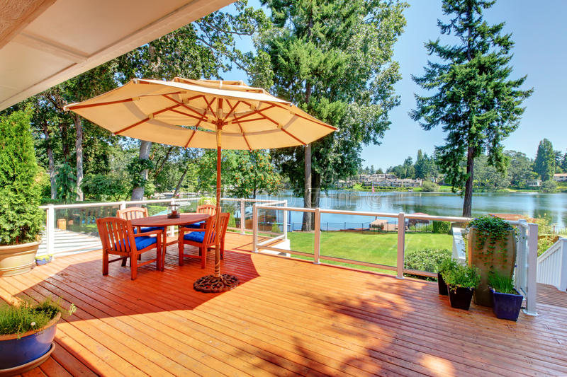 Sitting room area on screened walkout deck with patio table, umbrella and chairs. royalty free stock photos