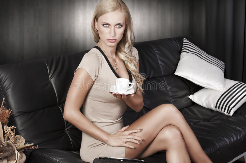 Sitting on sofa drinking from a cup stock photo