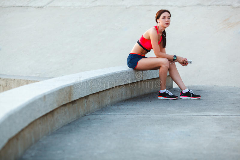 Sitting tired sporty woman stock photography