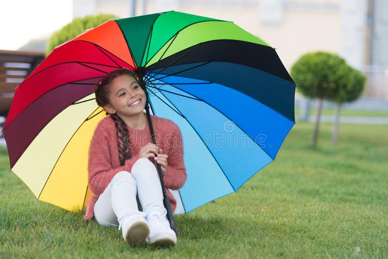 Sitting under umbrella and having fun. Small girl in park waiting for rain. Colourful umbrella as concept of happiness. Rainbow that can be touched. Happy stock photo