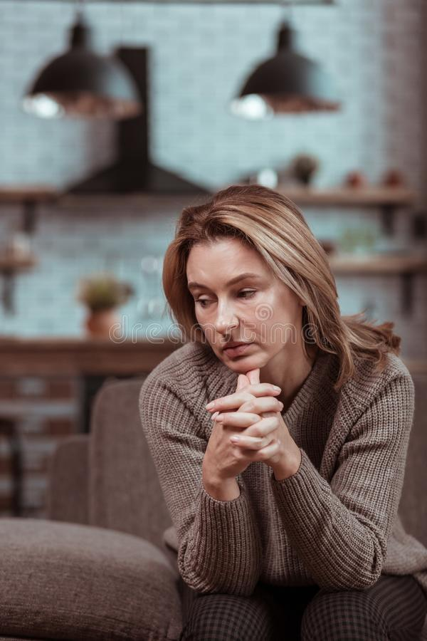 Blonde-haired housewife sitting and waiting for her husband coming home. Sitting and waiting. Blonde-haired housewife sitting and waiting for her husband coming royalty free stock images