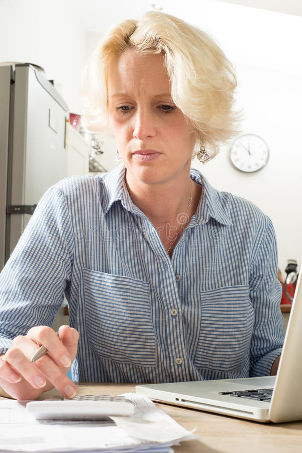 Sitting Woman Concentrates while Calculating Financials on Computer in Kitchen stock images