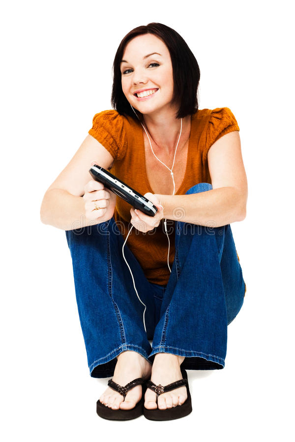 Sitting woman listening media player. Sitting woman listening to music on an media player isolated over white stock images