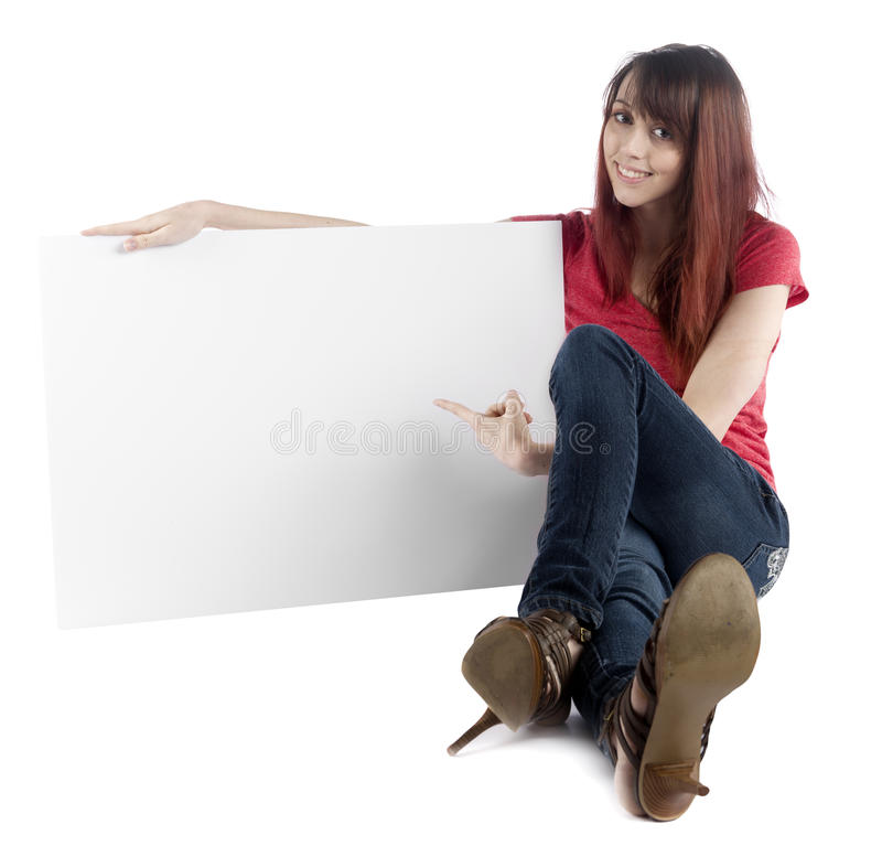 Sitting Woman Pointing at her Empty Cardboard. Close up Sitting Young Woman in Trendy Attire Pointing at her Empty White Large Cardboard, Emphasizing Copy Space stock image