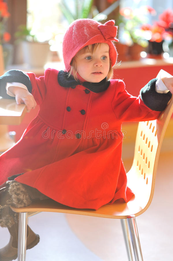 Sitting on a Yellow Chair. A little girl in red, sitting on a yellow chair royalty free stock images