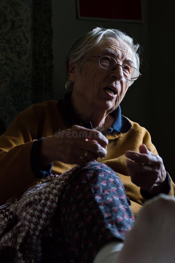 Sittingin mayor feliz de la mujer un cuarto oscuro que tiene conversación con su familia imágenes de archivo libres de regalías