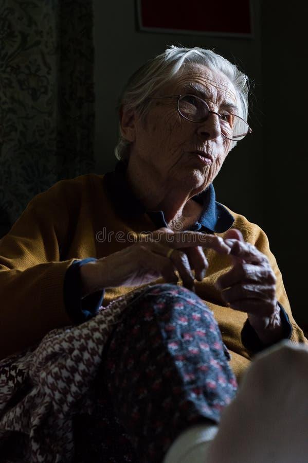 Sittingin mayor feliz de la mujer un cuarto oscuro que tiene conversación con su familia foto de archivo libre de regalías