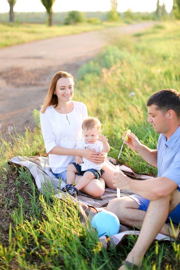 sittling在与一点婴孩和吹的泡影的草的年轻微笑的父母 免版税库存照片