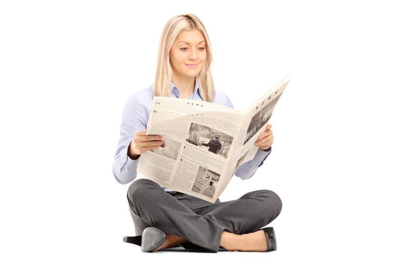 Sittng sonriente joven de la mujer en un piso y la lectura de un periódico imagen de archivo