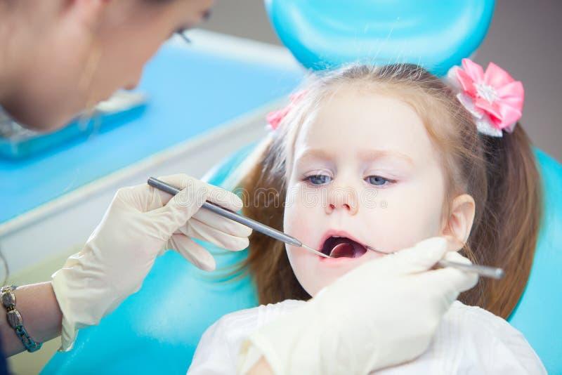 Sitts de petite fille dans le bureau du ` s de dentiste image stock