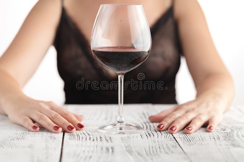 Situação bebendo do vinho tinto da mulher bonita em um sofá imagens de stock