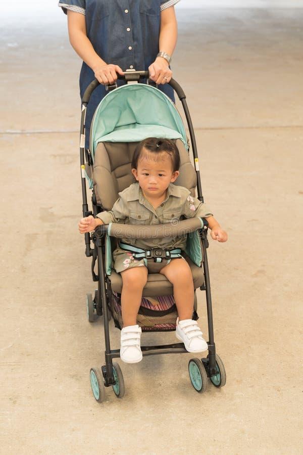 A situação bonito asiática do bebê no carrinho de criança com mãe ciao fotografia de stock