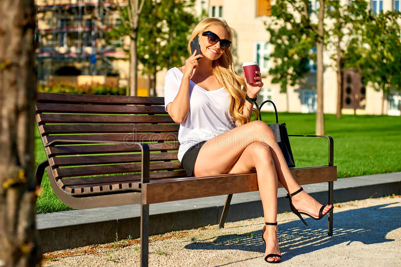 Situação da jovem mulher em um banco e fala em seu telefone imagem de stock royalty free